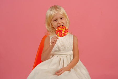 One giant whirly pop can last a very long time. Happy childhood food. Small girl hold lollipop on stick. Small child with sweet lollipop. Happy candy girl