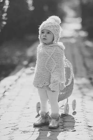 Toddler in knitted clothes playing outdoors