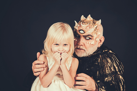 Fairytale concept. Senior man with white beard dressed like monster telling story to little girl. Man with thorns or wart with child sitting on his knees. Demon with third eye on black background.