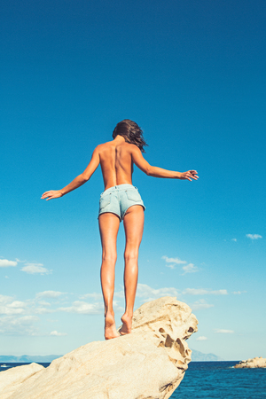 Freedom traveler woman standing topless with raised arms on the top of mountain and enjoy the beautiful of seascape. travel and freedom