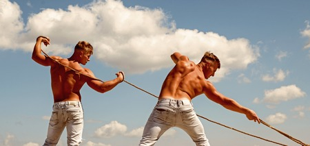 The meaning of a team. Strong men pull ropes. Twins men use muscular hand strength. Athletic twins with fit sexy body. Sport exercises for building strength and power Banco de Imagens - 115035271