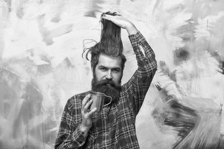 Bearded man holding stylish fringe hair and metal mug