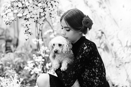 ordinary spanish woman with poodle dog pet in garden