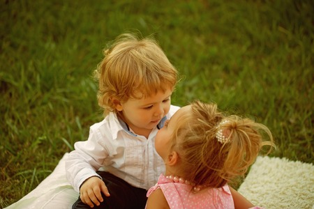 Sister kiss brother with blond hair on green grass Stock Photo