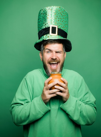 Happy St Patricks Day concept with pot of gold. Man on green background celebrate St Patricks Day. Patricks Day Pot of Gold and shamrocks.