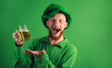 Patricks day party. Portrait of excited man holding glass of beer on St Patricks day isolated on green. Man in Patricks suit smiling.