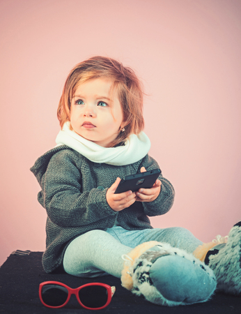 kid listen music with headset and mp3 on phone. winter kid fashion. small happy girl. little girl child smiling. childhood and happiness. Looking trendy. Hip hop girl. Stockfoto