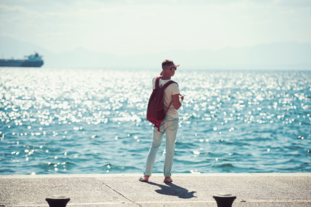 man traveler with backpack looking far away at sea water. travel and wanderlust concept. summer vacation and adventures. young man is going to marine trip. futute life concept. Imagens