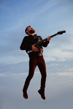 bearded hipster play guitar flying in blue sky.