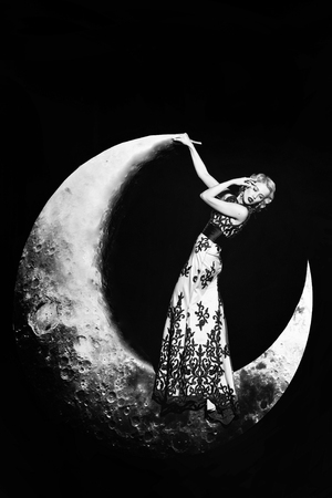 Beautiful young woman with blonde hair and red lips posing on crescent moon in long evening elegant dress with lace on black background