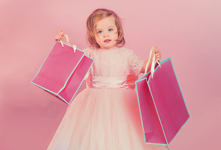 happy childhood of little girl. Kid shopping. shopping bags. Christmas gift. Thanks for your purchase. big sale in shopping mall. Happy birthday. New year party. small girl child with present package.
