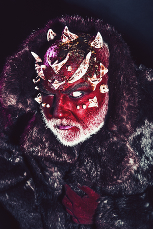 Senior man with white beard dressed like monster. Alien, demon, sorcerer makeup. Evil concept. Man with thorns or warts in fur coat. Demon with red face on black background, close up. Stock Photo