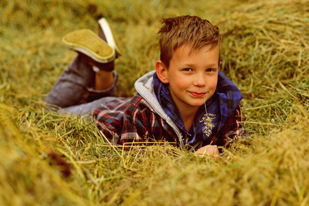 I am a village boy. Little boy in village. Little boy enjoy village life in countryside. Small child lie in hay in farm barn. A wonderful way to relax. Imagens