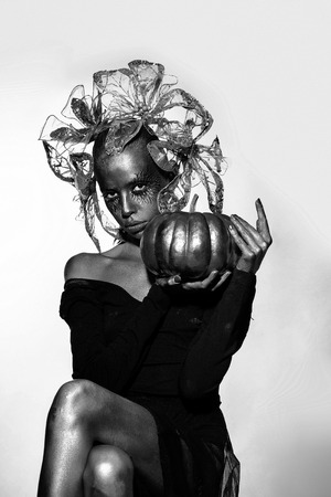 halloween golden woman or girl holding painted gold pumpkin has pretty face with makeup and body art metallized color with decorative flowers on head on white grey background