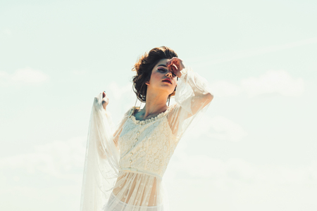 retro style and makeup for young woman in white dress. retro woman pose on blue sky background in vintage style.