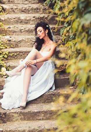 Sexy woman in stockings lingerie on wedding day. Woman wear lace garter on leg. Girl with bridal makeup and hairstyle. Bride in white dress sit on steps outdoor. Wedding fashion and accessory.