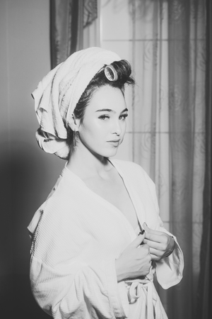 Girl with towel on head with nude chest. Sexy lady with calm face holds her robe. Woman in bathrobe with curler in hair at curtains on background. Morning routine concept.
