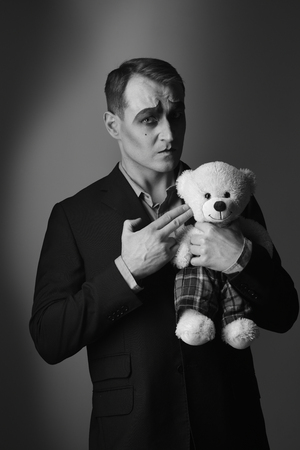 Theatre actor with hand gesture killing teddy toy. Stage actor shooter with mime makeup. Banco de Imagens