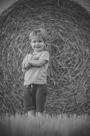 Adorable young toddler boy standing by haystacks