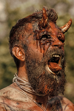 Halloween devil head with bloody horns. Demon man with beard showing tongue. Vampire or dragon with open mouth. Satan with red blood and wounds on face. Hell, evil, horror, darkness concept. Stock Photo