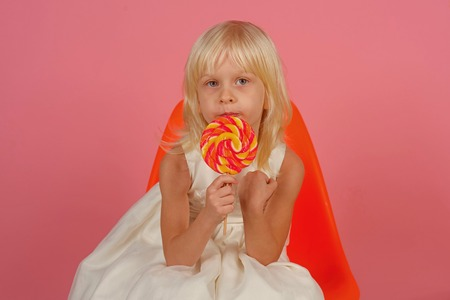Little child with sweet lollipop. Happy candy girl. Little girl hold lollipop on stick. Happy childhood food.