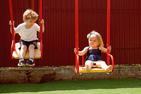 Small children with blond hair on swing. Small brother and sister enjoy playing together. Stock Photo
