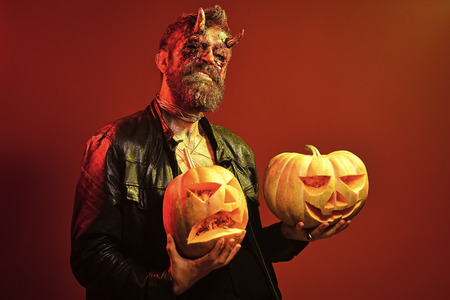 Halloween devil with bloody horns, eyes, red blood, wounds. Man demon hold pumpkins on orange background. Darkness and light concept. Trick or treat. Satan with jack o lanterns.