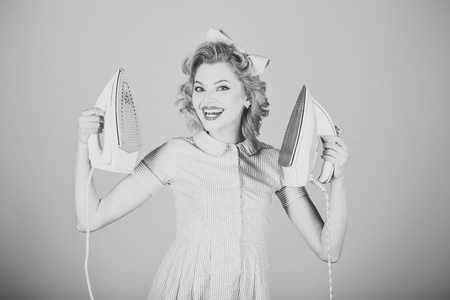Pinup woman hold iron, retro style, maid. Housekeeper in uniform with iron, household. Order services, wife, gender equality. Everyday life, housework. Retro woman ironing clothes, gender inequality. Foto de archivo - 118683806