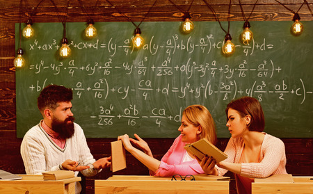 Girls students and bearded teacher, lecturer, professor. College and education concept. Students, young scientists studying, holds book , while professor teaches, explains, chalkboard background.