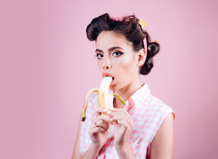 pretty girl in vintage style. pinup girl with fashion hair. banana dieting. pin up woman with trendy makeup. retro woman eating banana, copy space. Taking order on fruits.