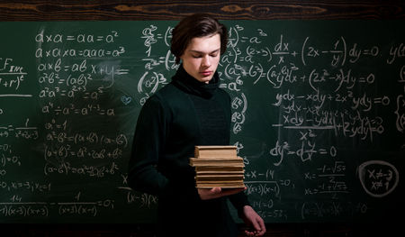 Teaching private classes is one of the best options for teacher now. Modern teacher hipster writing on big blackboard with math formula. Trying student is the one that has the most potential Stock Photo
