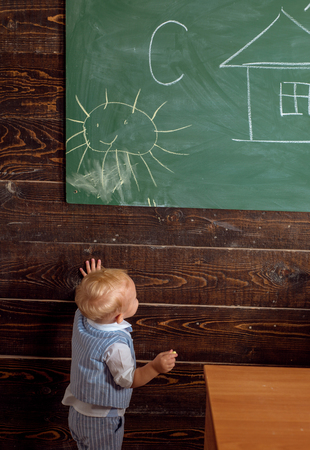 Small child painting picture on classroom chalkboard. Toddler in school of painting. Every artist was first an amateur. 版權商用圖片