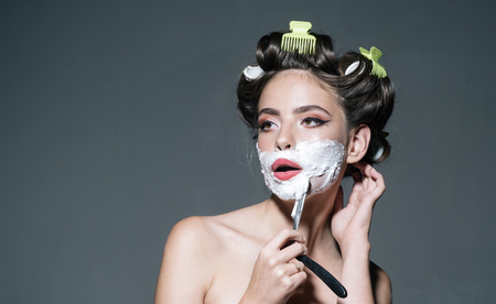 morning grooming and skincare. girl with fashion hair. retro woman shaving with foam and razor blade. pin up woman with trendy makeup. pretty girl in vintage style, copy space. Clean and dry shaving.