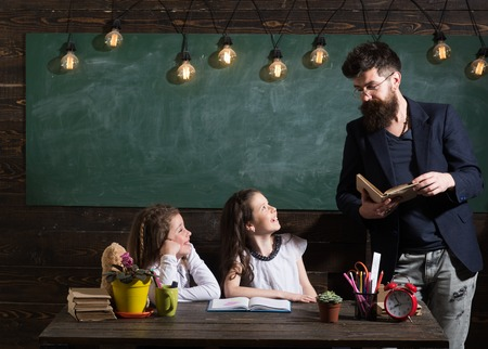 Teacher and girls pupils in classroom, chalkboard on background. Man with beard teaches schoolgirls, reading book. Curious cheerful children listening teacher with attention. Primary school concept