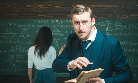 Teacher man using glasses scared in shock, expressing panic and fear at classroom. Foto de archivo