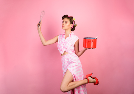 retro woman cooking in kitchen. pinup girl with fashion hair. perfect housewife. pin up woman with trendy makeup. pretty girl in vintage style. Enjoying new day. 写真素材