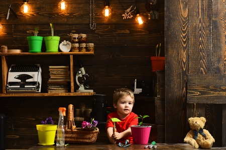 Planting concept. Little boy with gardening tools for planting. Planting a flower in pot. Hand planting. All the flowers of tomorrow are in the seeds of today. Reklamní fotografie