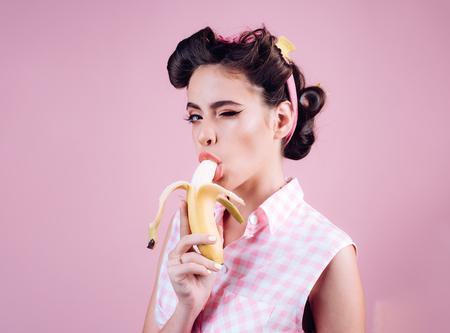 hübsches Mädchen im Vintage-Stil. Pinup-Girl mit Modehaar. Bananen Diät. Pin-up-Frau mit trendigem Make-up. Retro-Frau, die Banane isst. kokett fühlen.