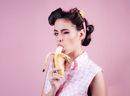 pretty girl in vintage style. pinup girl with fashion hair. banana dieting. pin up woman with trendy makeup. retro woman eating banana. feeling flirty. Banco de Imagens - 115475195