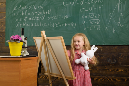 Child painting picture on easel in art studio. Little girl learn art drawing picture. Archivio Fotografico - 115475174