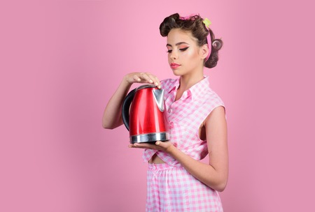 perfect housewife. pin up woman with trendy makeup. pinup girl with fashion hair. retro woman cooking in kitchen. pretty girl in vintage style. presenting product.