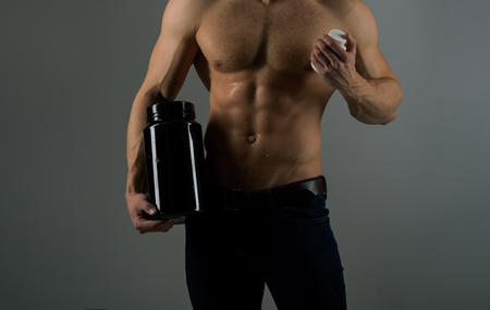 Diet effect. Strong man hold vitamin bottles. Healthy diet. Man with six pack abs. Stimulating muscle growth with anabolic steroids. Anabolic hormone increases muscle strength. Vitamin nutrition.