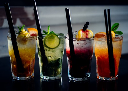 A full measure of bars. Cocktail drinks served in glasses with straws. Iced drinks in cocktail glasses. Alcoholic mixed drinks with ice. Juicy beverages with alcohol on counter. Alcohol addiction.
