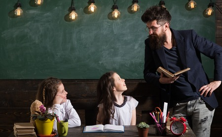 Man with beard teaches schoolgirls, reading book. Curious cheerful children listening teacher with attention. Teacher and girls pupils in classroom, chalkboard on background. Primary school concept Zdjęcie Seryjne