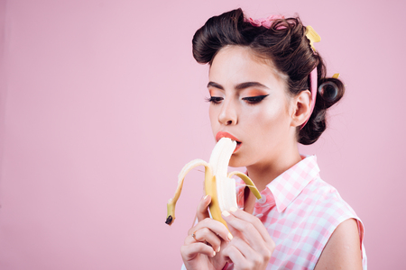 pin up woman with trendy makeup. retro woman eating banana. pinup girl with fashion hair. pretty girl in vintage style. banana dieting, copy space. i want you.