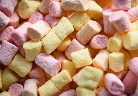 Gummy and fluffy. Marshmallow souffle with sweet flavor. Marshmallow recipe with sugar and gelatin. Sweet snack food. Unhealthy junk food. Colorful mini marshmallow background or texture.