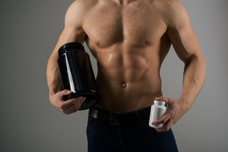 Transforming body with diet. Anabolic hormone increases muscle strength. Strong man hold vitamin bottles. Man with six pack abs. Muscle growing with anabolic steroids. Vitamin nutrition. Healthy diet. 免版税图像