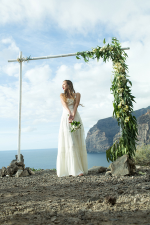 Pretty girl or beautiful bride, young, sexy woman in white dress with wedding bouquet stands under wooden or bamboo arch with flowers decorations on mountain top on sunny day on blue sea background
