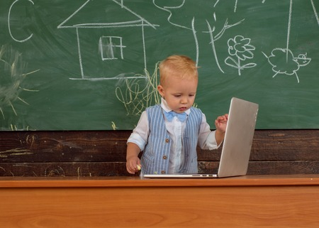 Early development with new technology in primary school. Little boy learn using laptop computer, early development.