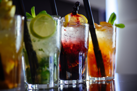 Alcohol addiction. Cocktail drinks served in glasses with drinking straws. Iced drinks in cocktail glasses. Alcoholic mixed drinks with ice. Juicy alcohol beverages on bar counter. Drinking all day. Stock Photo